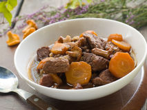 Beef ragout. (Boeuf Bourguignon) with carrots, chanterelles and onions, selective focus Royalty Free Stock Photos