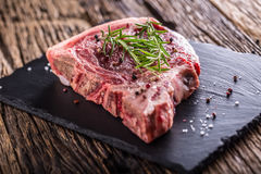 Beef raw steak. Raw fresh T-bone steak with salt pepper and rose Stock Images