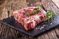 Beef raw steak. Raw fresh T-bone steak with salt pepper and rose Royalty Free Stock Image