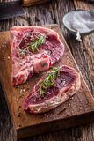 Beef raw steak. Raw fresh T-bone steak with salt pepper and rose Royalty Free Stock Photography
