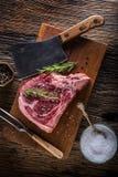 Beef raw steak. Raw fresh T-bone steak with salt pepper and rose Stock Image