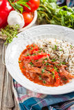 Beef with red pepper, stewed in tomato sauce garnished with a mixture of basmati and wild rice Stock Image