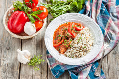 Beef with red pepper, stewed in tomato sauce garnished with a mixture of basmati and wild rice Stock Photos