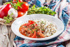 Beef with red pepper, stewed in tomato sauce garnished with a mixture of basmati and wild rice. Beef stew in tomato sauce with red peppers. a side dish of Stock Images