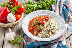 Beef with red pepper, stewed in tomato sauce garnished with a mixture of basmati and wild rice Stock Photo