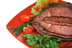 Beef on red plate over white Royalty Free Stock Photo