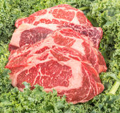 Beef rib eye on the salad leafs. Dry aged rib eye steaks on the salad leafs Royalty Free Stock Photo