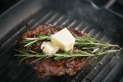 Beef rib eye steak with rosemary on grill pan closeup Stock Photos