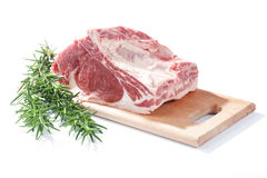 Beef ribs. And rosemary on a wooden cutting board stock image