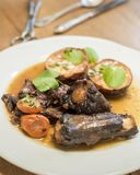 Beef ribs with roasted new potatoes. Carrots and wine Stock Image