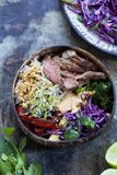 Beef with rice, red cabbage and broccoli. Bowl with sliced beef steak, broccoli, red cabbage, broccolli sprouts and satay sauce royalty free stock photo