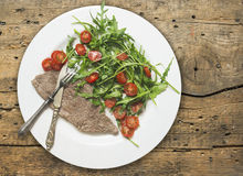 Beef with rocket salad and tomatoes on old wood Royalty Free Stock Photos