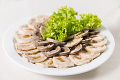 Beef roll with dried apricots and salad closeup. Cold appetizer meat roll with dried apricots Stock Image
