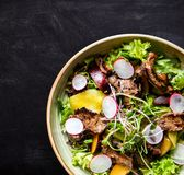 Beef salad with radish, peach and green vegetables stock image