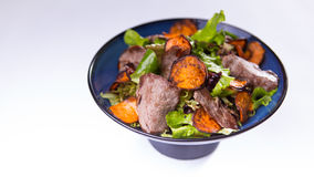 Beef salad with sweet potatoes in blue chinese bowl on white bac Royalty Free Stock Image