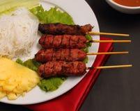 Beef salad Vietnam style. Vietnam beef on sticks served with salad on a black background Stock Photos