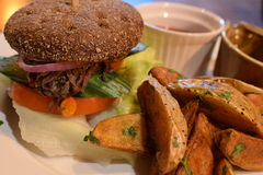 Beef Sandwich Dark Bun. A Shredded Beef sandwich on a dark bun. Served with a side of home style fries stock images