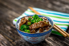 Beef in sauce with broccoli and rice. On wooden background Royalty Free Stock Image
