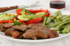 Beef with sausages, beans and salad Royalty Free Stock Photo
