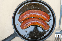 Beef sausages cooked on iron skillet Royalty Free Stock Image