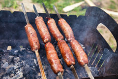 Beef sausages grilled on a coals. Barbecue on brazier. Stock Images