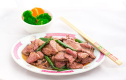 Beef and Scallion Stir-Fry. Marinated Beef and Scallion Stir-Fry with a vegetable (Broccoli and Carrot) side-dish.  A pair of chopsticks is also in this photo Royalty Free Stock Images