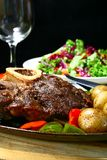 Beef shank. Juicy beef shank served on a sizzling iron plate royalty free stock photo