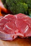 Beef Meat. Uncooked cow shank meat on the wooden board with vegetables royalty free stock images