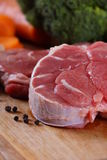Beef Raw Meat and Pepper. Uncooked cow shank meat on the wooden board with vegetables and black pepper stock image