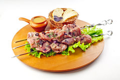 Beef  shish kebab. Beef shish kebab  with seasoning, bread and greens on the woody plate Stock Photos
