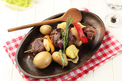 Beef shish kebab. And new potatoes on cast iron plate Royalty Free Stock Photo