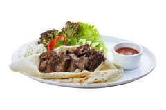 Beef shish kebab in pita bread. On a white plate royalty free stock photo