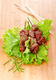 Beef Skewers. BBQ beef on a stick on the leaves of lettuce Royalty Free Stock Images