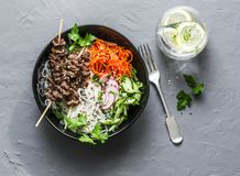 Beef skewers, rice vermicelli, pickled vegetables salad carrots, cucumbers, radishes, greens and lemon thyme lemonade on grey back Royalty Free Stock Photos