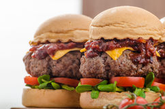 Beef Sliders with homemade barbecue sauce. Cheddar, cherry tomatoes and microgreens Royalty Free Stock Images