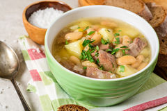 Beef soup with potatoes, beans and leeks in ceramic bowl on stone background. Selective focus royalty free stock image