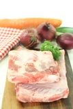 Beef spare ribs with carrot. Beef spare ribs with parsley and carrot on a wooden board Royalty Free Stock Image