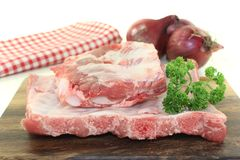 Beef spare ribs with parsley and onions. On a wooden board in front of light background Royalty Free Stock Photos