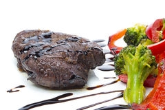 A beef stake with steamed green arranged on a white plate Royalty Free Stock Photos