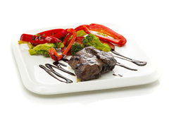 A beef stake with steamed green arranged on a white plate Stock Photos