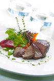 Beef Steak. A large serving of steak with a colorful variety of vegetables and garnished and dressed to appetizing taste on a plate Stock Image