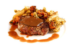 Beef Steak. A meal of rare filet mignon, with pasta vegetable salad. Isolated on white stock photos
