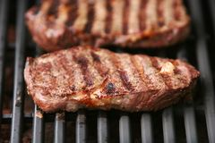Beef steak. Being grilled on a barbeque grill Stock Image