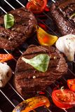 Beef steak on a barbecue grill. With vegetables stock images