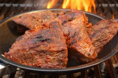 Beef Steak on the BBQ Grill with flames. Royalty Free Stock Images