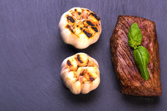 Beef Steak on black board. Tasty Beef Steak with garlic and basil on black board, backgrouund royalty free stock images