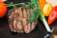 Beef steak on black plate with some vegetables Royalty Free Stock Photo