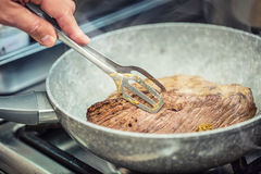 Beef steak. Chef in a restaurant kitchen use ceramic pan for preparation of beef steak Stock Images