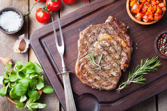 Beef steak with cherry tomato and rosemary on a dark cutting board Wooden background Top view Royalty Free Stock Photography