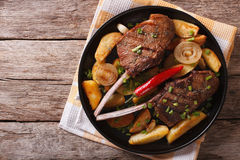 Beef steak with chili and fried potatoes. Horizontal top view Stock Image